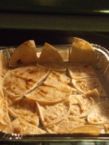 Preheat the oven to 350 degrees. While it warms up, use the back of a spoon to smear roasted garlic cloves generously all over the tortillas, drizzle on a little olive oil, and use the spoon to spread that love around on top of the garlic, without letting the tortilla get soggy. Quarter the tortillas, lay them on a baking sheet and pop them in the oven when it's warm enough. I made do with one of those giant foil pans that you get massive take-out/buffet food in.