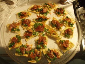 Top each taquette with a piece of arugula (fold the leaves if you have to) and prosciutto. If there are any tortillas that curled up in the oven, don't worry, they look cooler and it's more fun to tuck stuff inside them.
