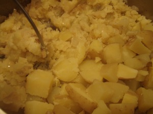 Combine the potatoes and onions (don't lose any of the melted butter!), add in the other 1/4 cup of butter, pick up your weapon of choice, and start mashing away, folding the mess every now and then to incorporate the onion bits.
